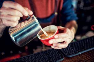 Barista creating latte art on long coffee with milk. Latte art in coffee mug. Barman pouring fresh coffee