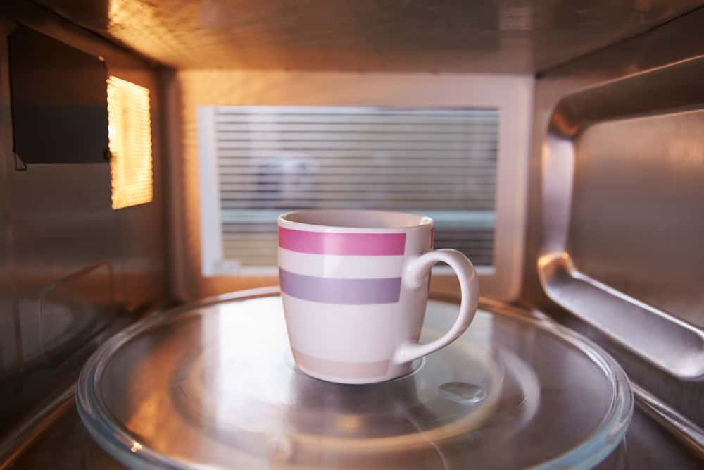 Warming Cup Of Coffee Inside Microwave Oven