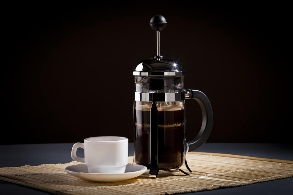French press coffee maker and coffee cup studio lit on table with dark background