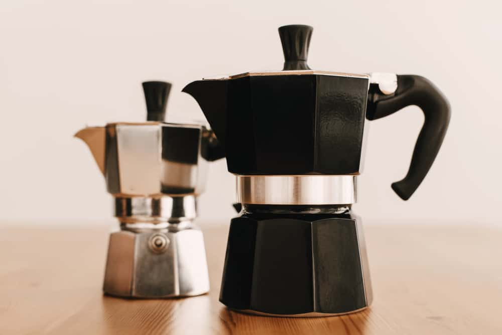 Steel and black geyser coffee makers on wooden table. Alternative coffee brewing method. Stylish accessories and items for alternative coffee