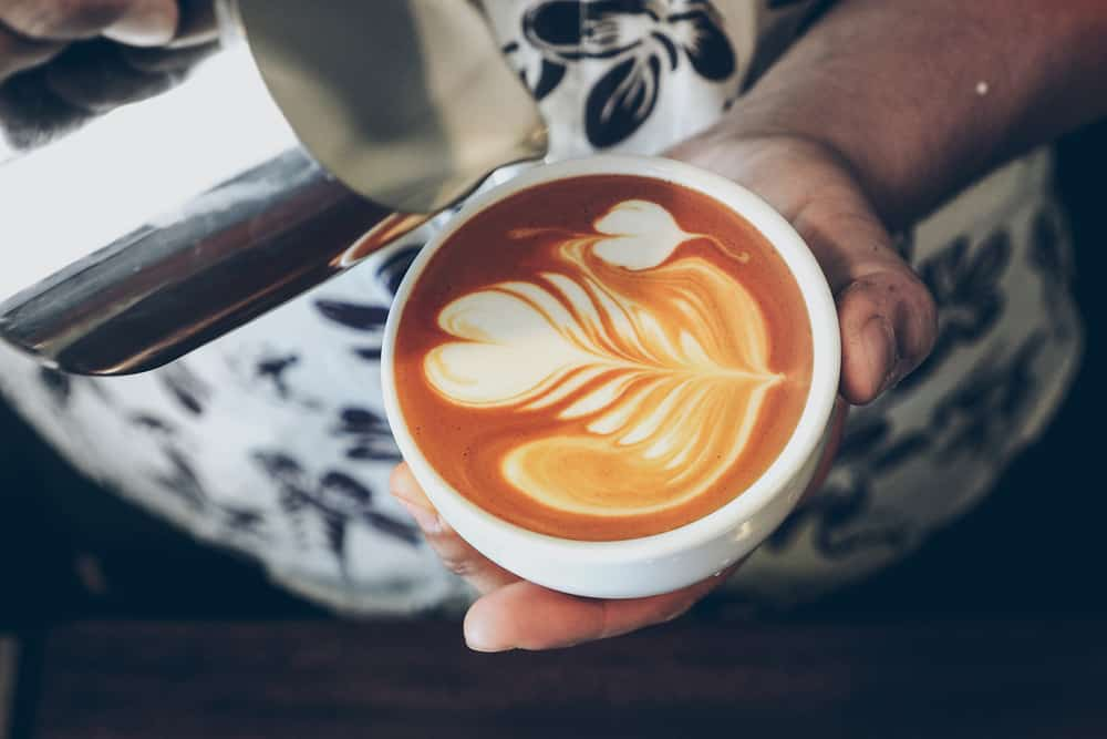 cup of coffee latte art on the wood background in vintage color style
