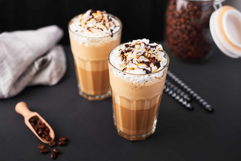 Iced latte coffee in a tall glass with caramel and chocolate syrup and whipped cream.