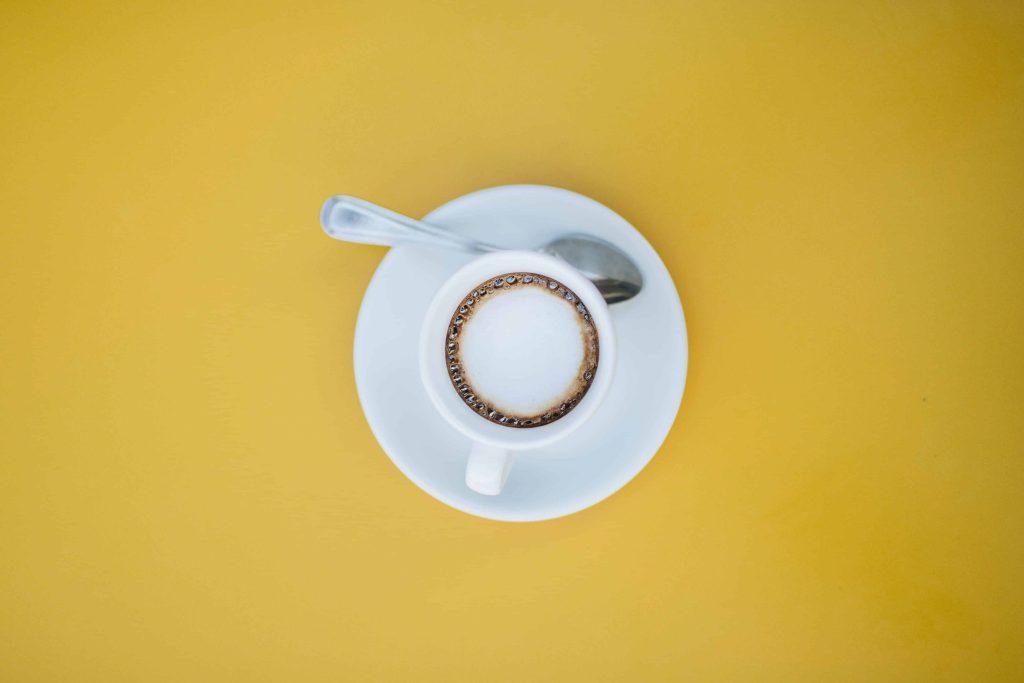 Espresso macchiato on yellow background