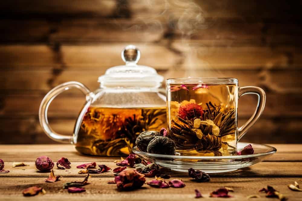 herbal tea in transparent teapot and teacup