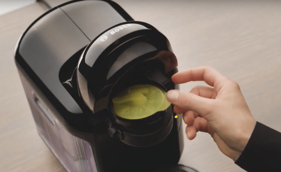Hand inserting a yellow service T-Disk into TASSIMO machine.