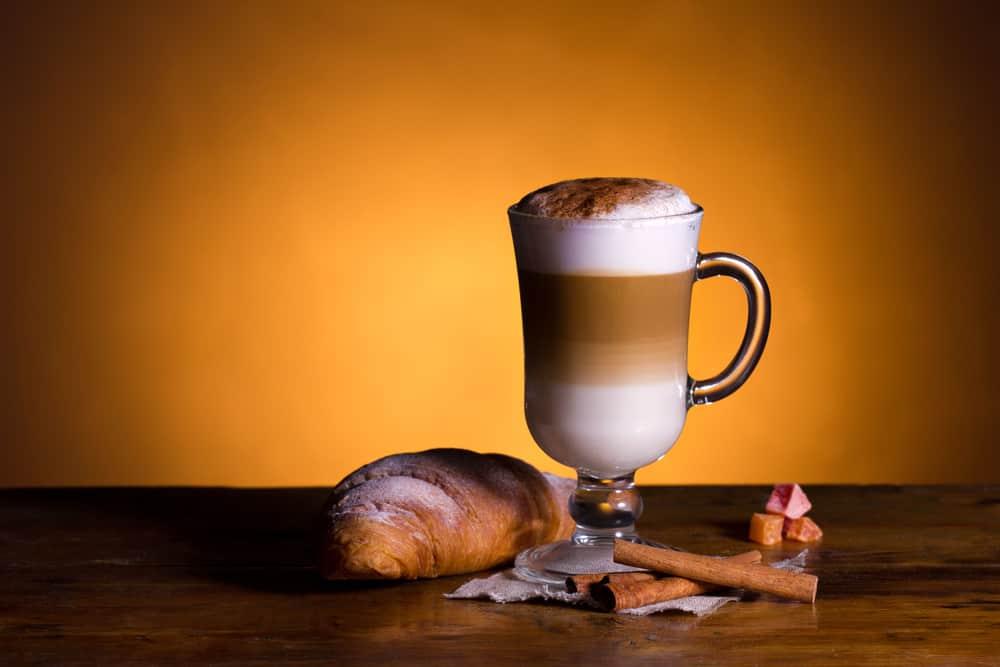 Latte macchiato next to a croissant on table