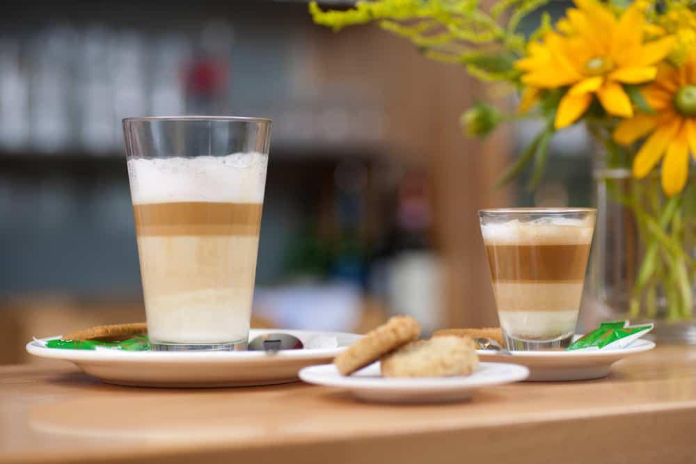 What is a macchiato? Two glasses of macchiato on a table.