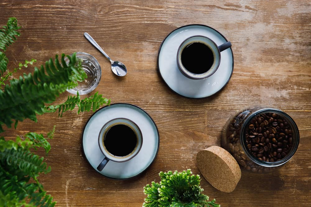 how many calories in a cup of coffee? Two black coffees and a jar of coffee beans on a table