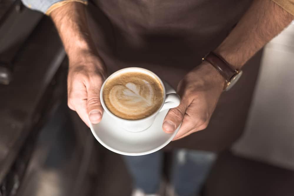 barista holding a mug containing a cappuccino