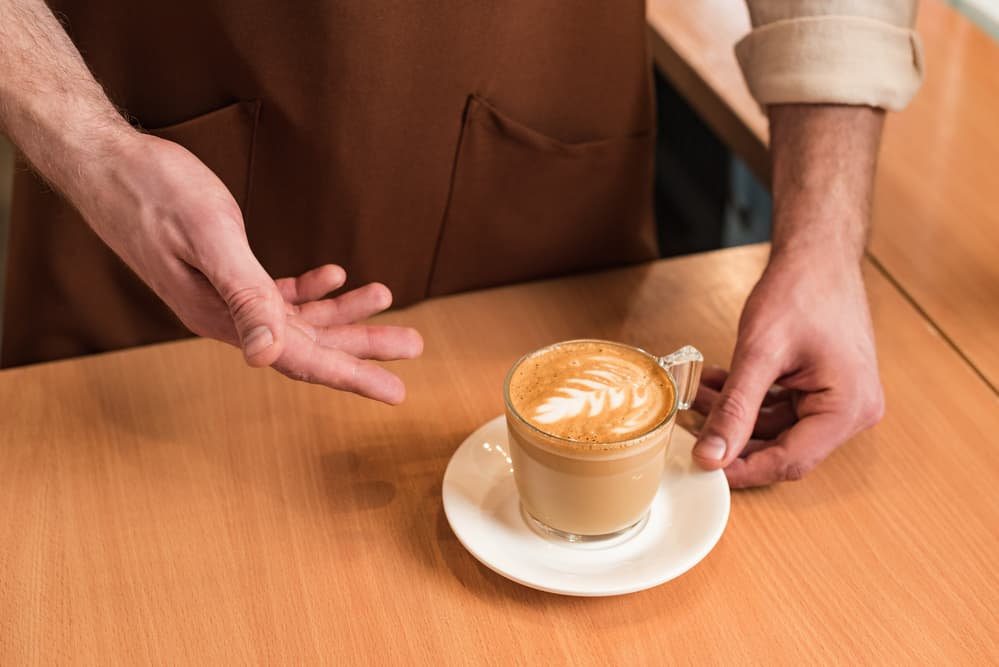 barista gesturing towards flat white on table