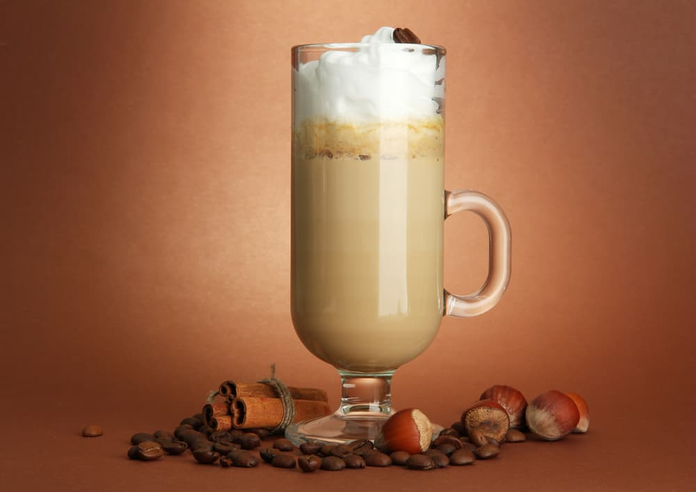 latte in a glass surrrounded by spices