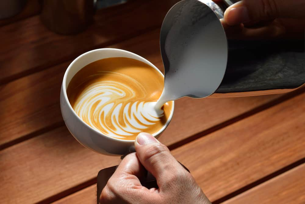 milk being poured into cup to create latte art