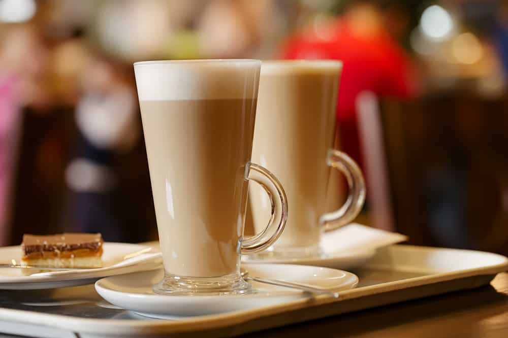 two tall glasses of lattes on a tray with a blurred background