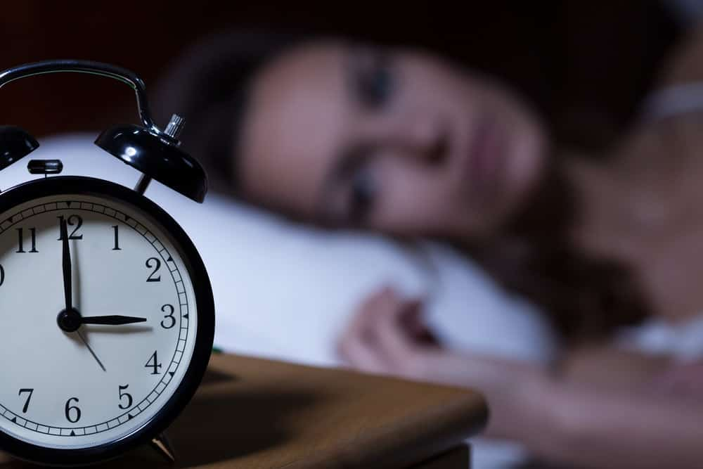 Close-up of alarm clock on night table with blurred out woman in background