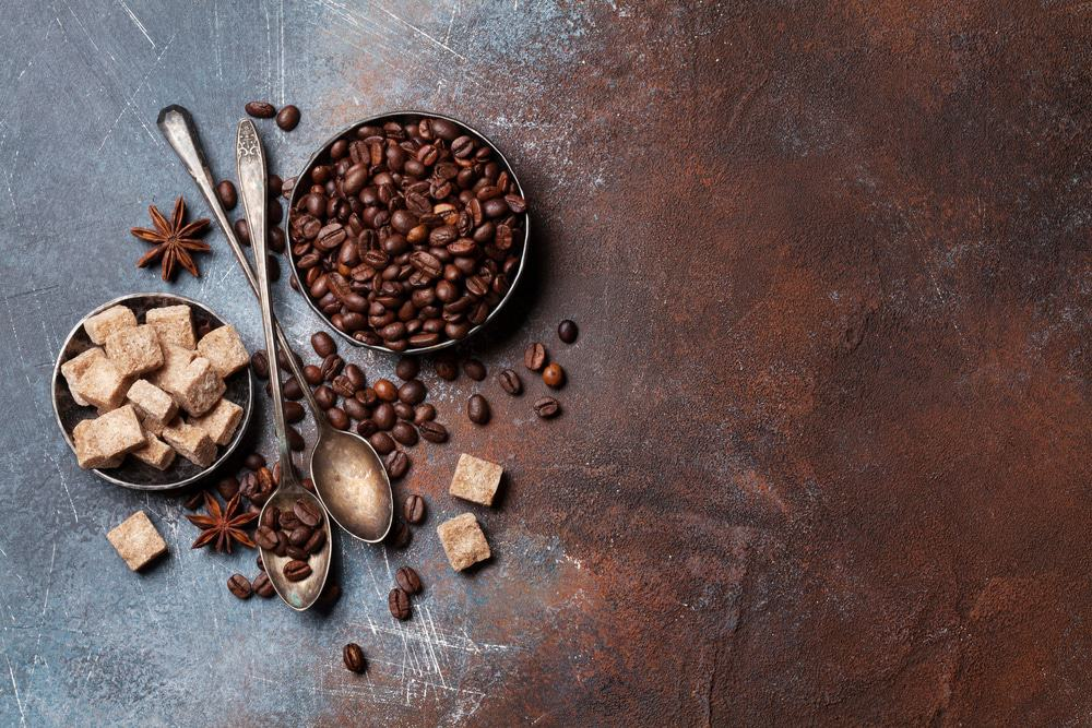 Coffee beans and sugar cubes on brown background