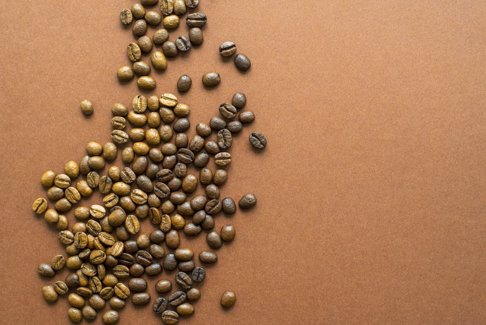 Light and dark roasted coffee beans together on brown background