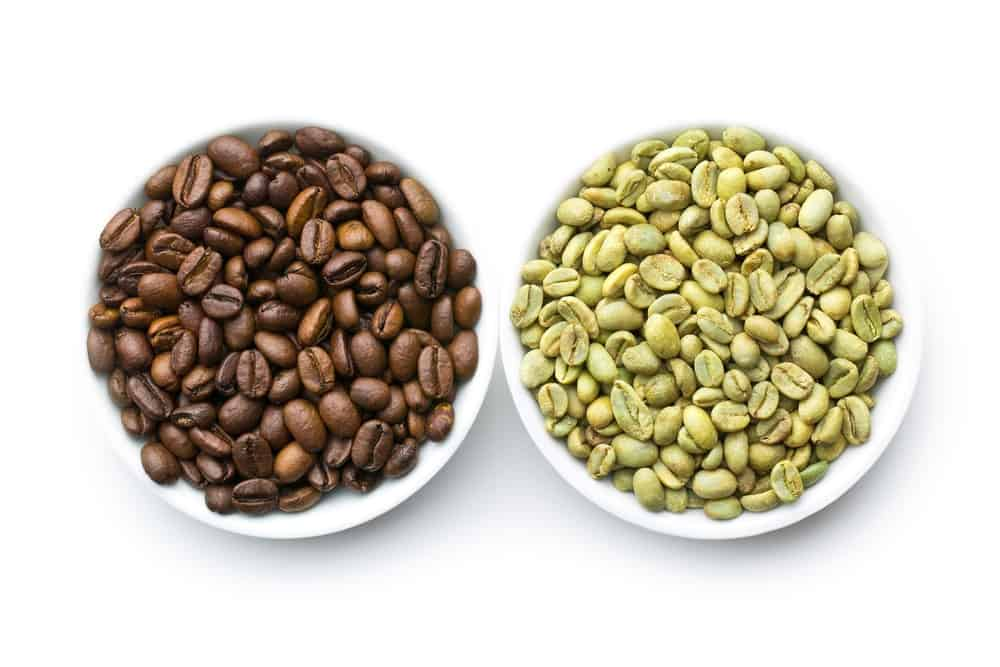 roasted and raw coffee beans in two bowls on white background